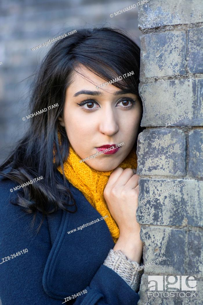 Stock Photo: Young woman standing behind a wall outdoors.