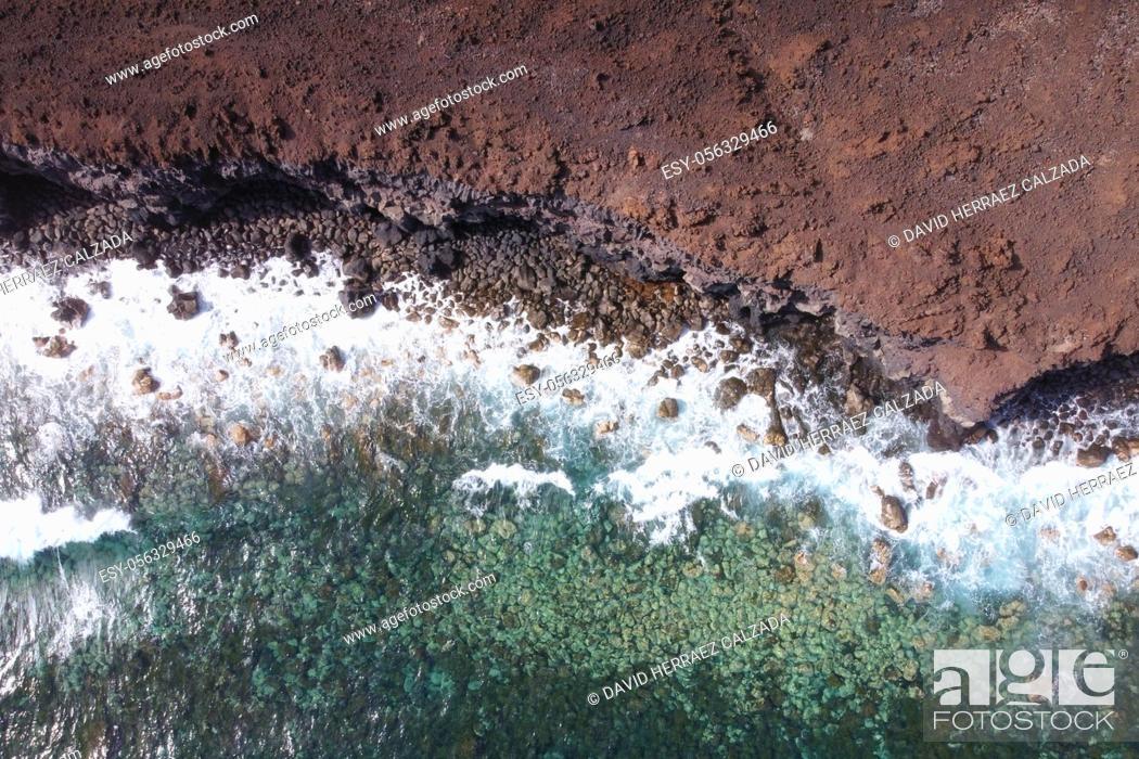 Stock Photo: Aerial top view of waves splashing on rocky volcanic coastline. High quality photo.