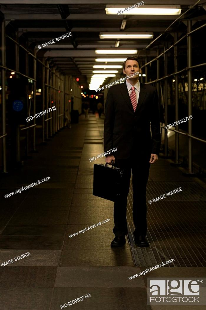 Stock Photo: Businessman standing on a walkway.