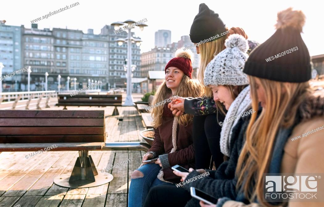 Stock Photo: Spain, Gijon, four friends using their cell phones outdoors.
