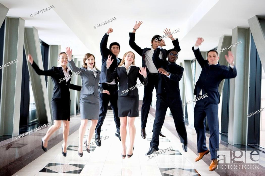 Stock Photo: Business people jumping with hands outstretched and smiling together.