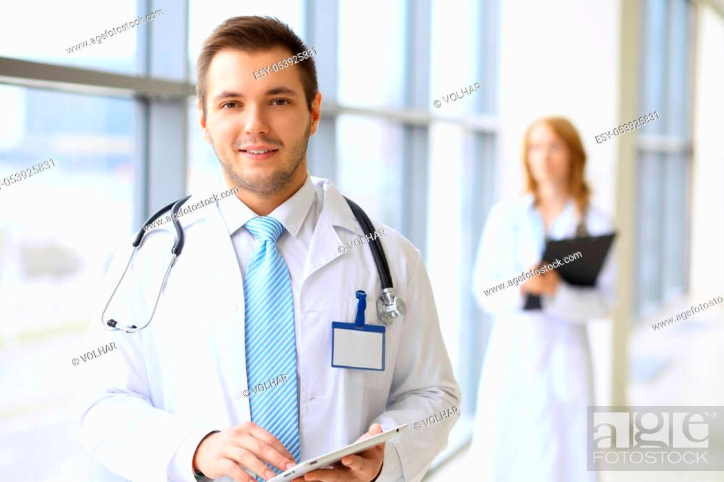 Stock Photo: Smiling doctor waiting for his team while standing upright.