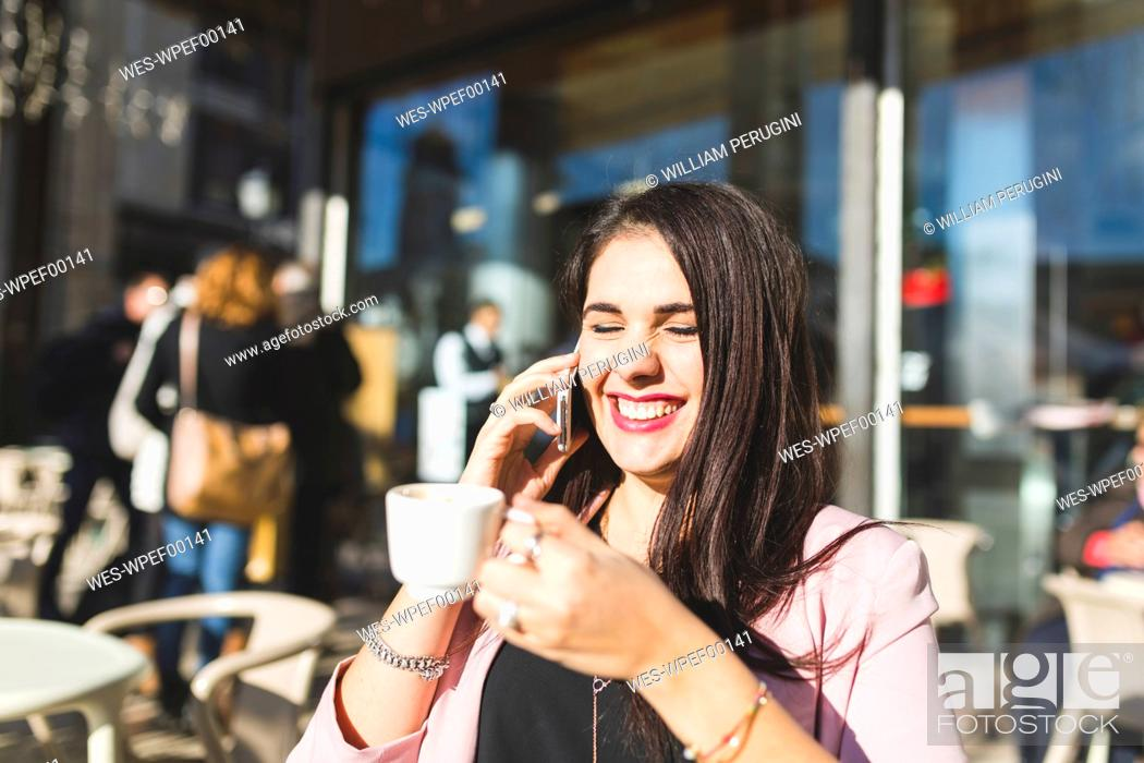 Stock Photo: Laughing young businesswoman on cell phone at an outdoor cafe.