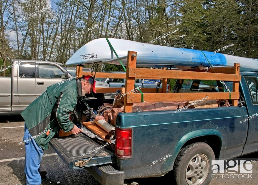 Stock Photo: This middle aged Caucasian man is preparing the back of his truck with camping gear with a kayak loaded on top in readiness for a camping trip.