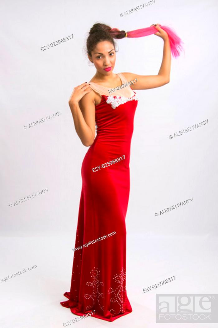 Stock Photo: Mulatto girl dancer performs a dance elements, isolated on a light background.