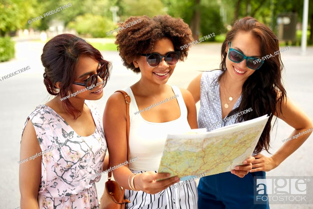 Photo de stock: happy women with map on street in summer city.