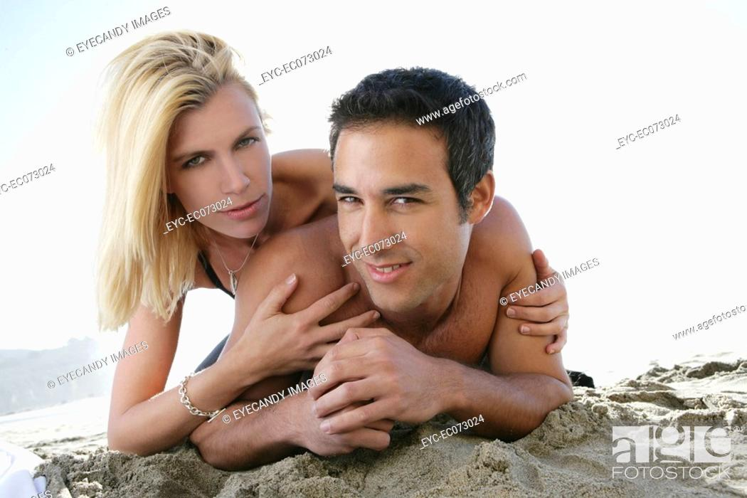 Stock Photo: Young nude couple relaxing on beach.