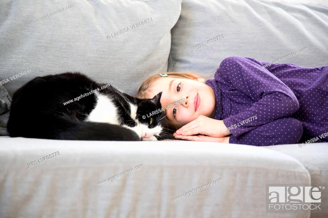 Stock Photo: Portrait of little girl lying on couch with cat.
