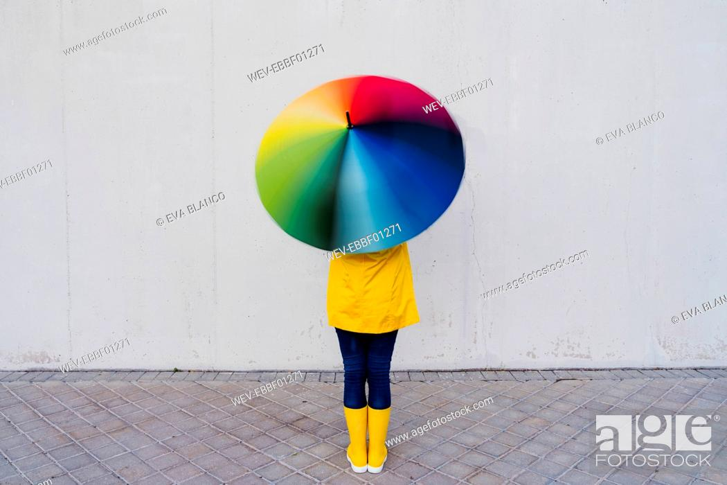 Stock Photo: Woman holding colorful umbrella standing in front of gray wall on footpath.