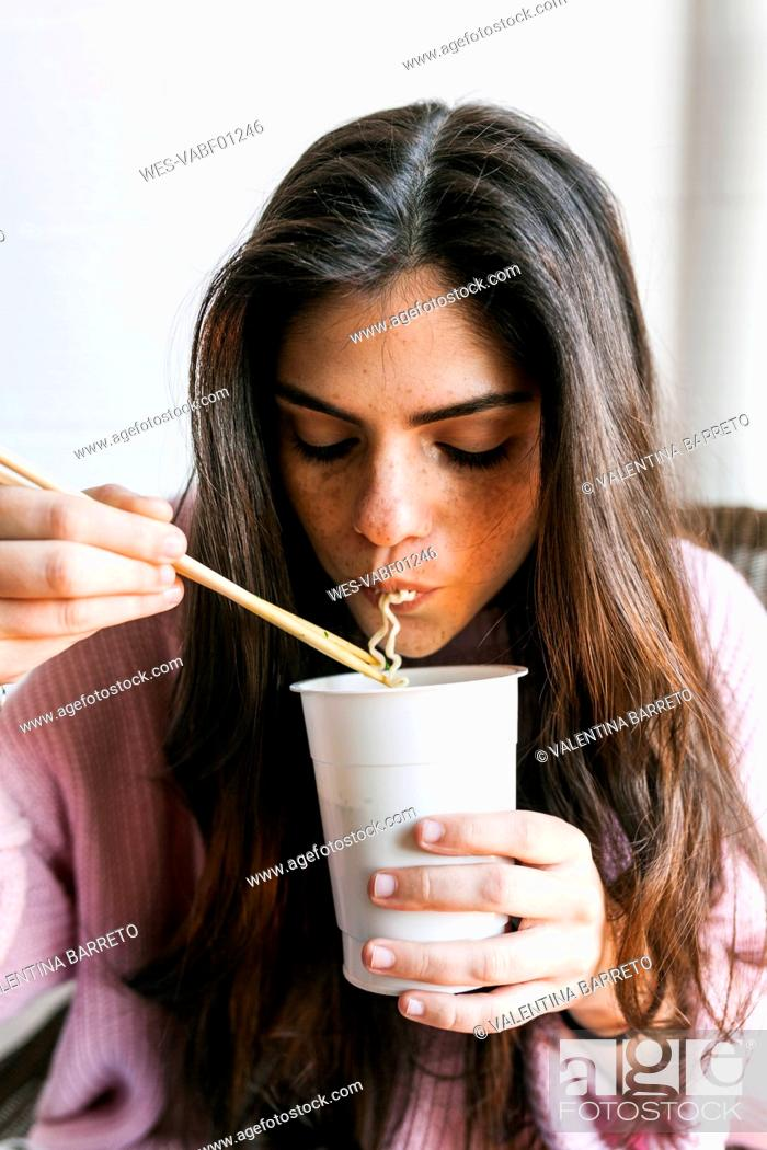 Stock Photo: Young woman eating Chinese noodles.