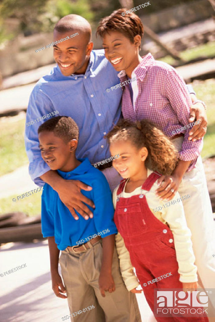 Stock Photo: Young couple standing outdoors with their son and daughter.