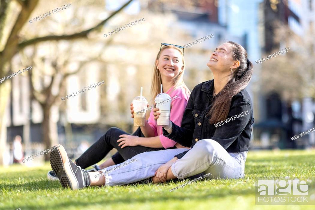 Stock Photo: Cheerful female friends having milkshake in public park.