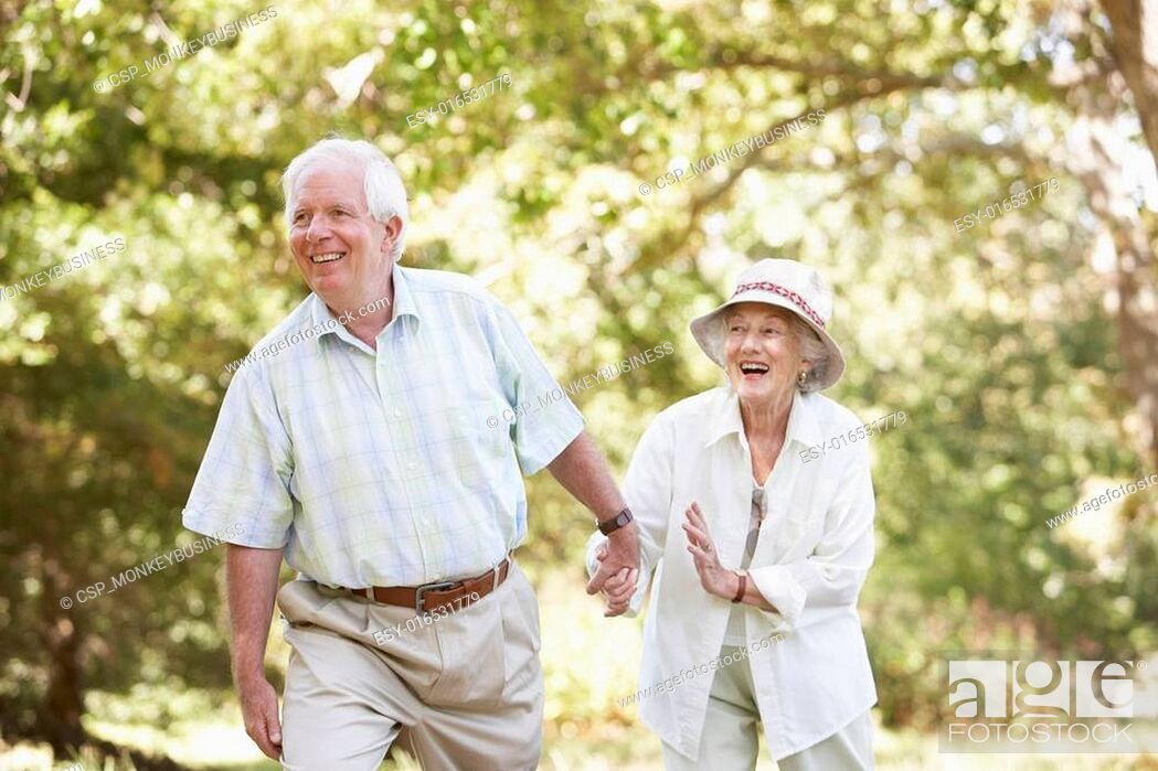 Stock Photo: Senior Couple Walking In Park.