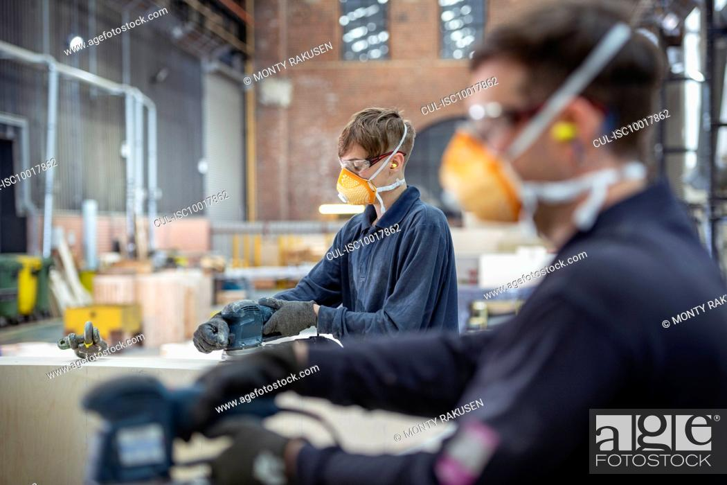 Stock Photo: Apprentice working on wooden mould in steelworks.
