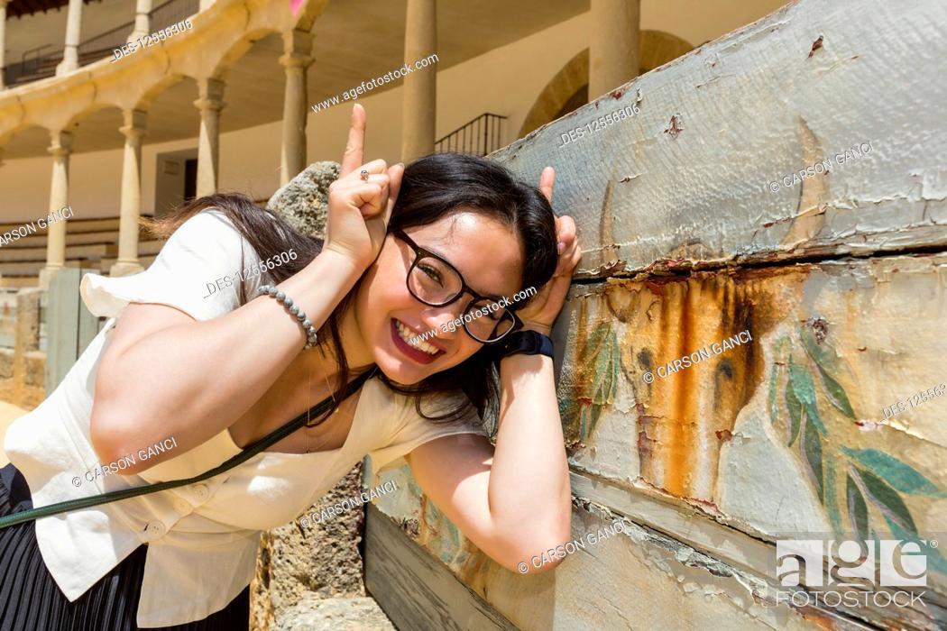 Imagen: Young female tourist poses with bull image at bull fighting ring, Plaza de Toros de Ronda; Ronda, Malaga, Andalucia, Spain.