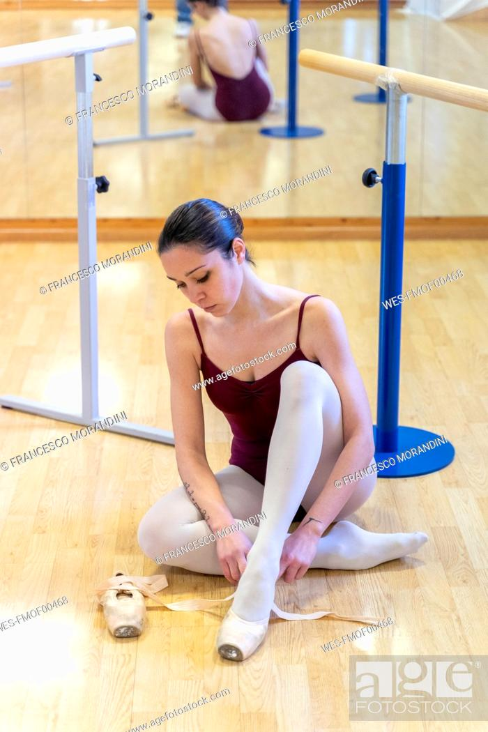 Stock Photo: Ballet dancer putting on shoes.