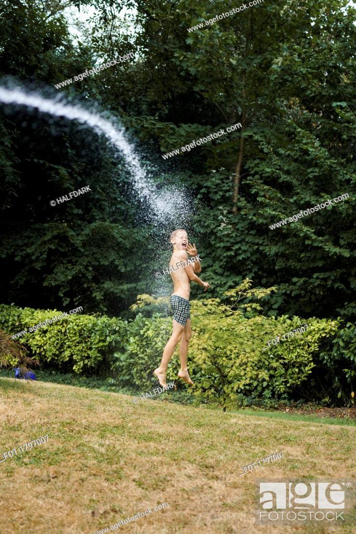Stock Photo: Water spraying boy in swim trunks in backyard.