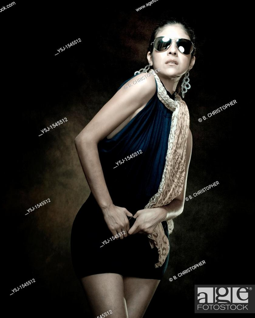 Stock Photo: A fashionable young woman wearing a one-piece and sunglasses in the studio.