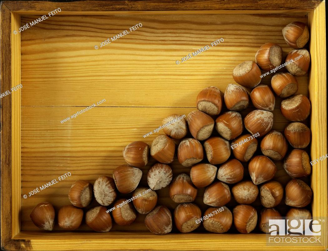 Stock Photo: Hazelnuts in triangle on wooden box background. Copy space.
