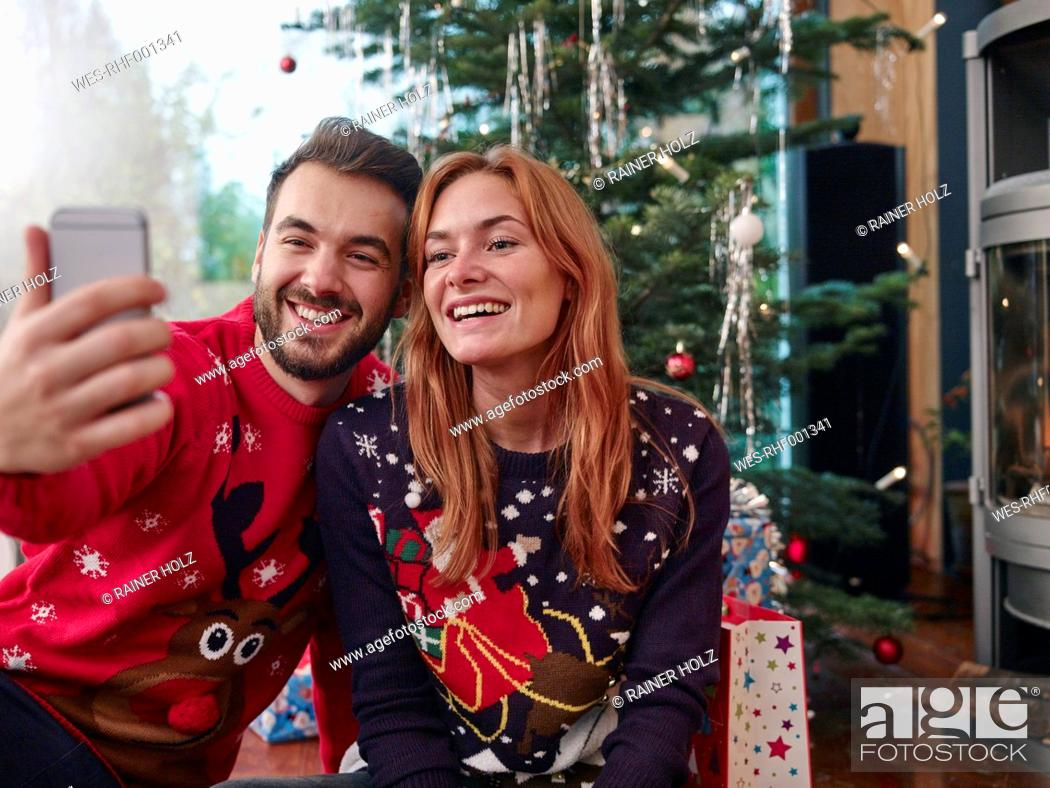 Stock Photo: Happy couple taking selfie in front of Christmas tree.