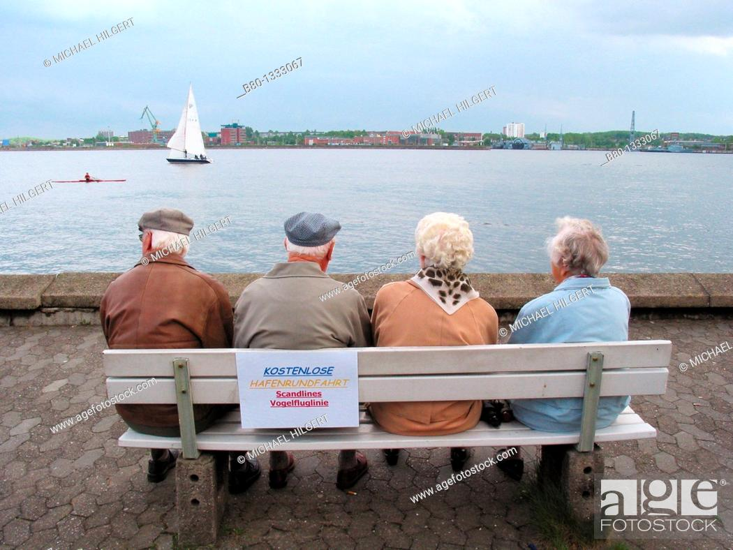 Stock Photo: Old couples at free harbour watching sailing boat, Kiel, Germany.