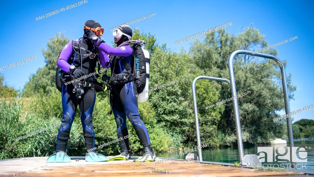 Stock Photo: 31 July 2020, Lower Saxony, Hemmoor: Agnieszka Hrywniak (l) and Anna Wisniowska from Poland are preparing for the dive in the chalk lake.