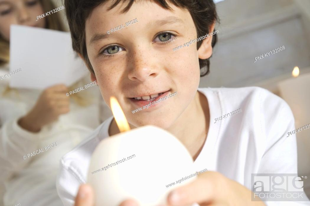 Stock Photo: Portrait of a little boy holding a candle, sister in background, indoors.
