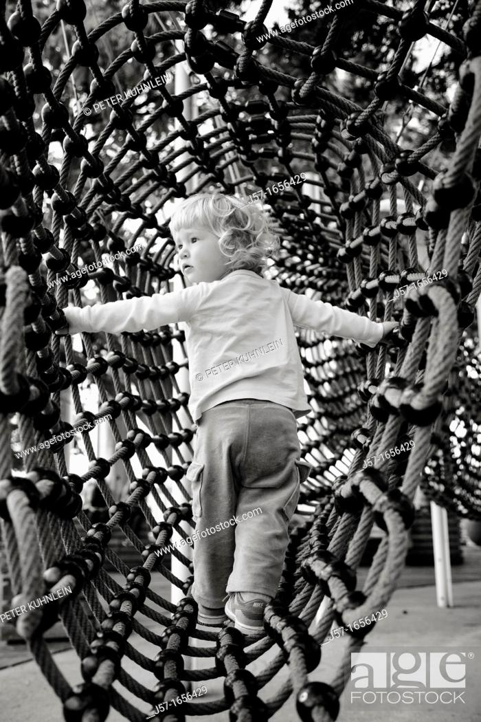 Stock Photo: Young girl playing in a rope net playground in Zurich, Switzerland.