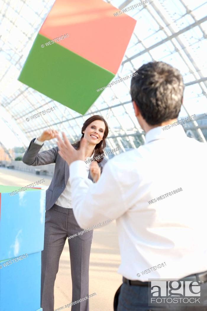 Stock Photo: Germany, Leipzig, Business people playing with cubes.