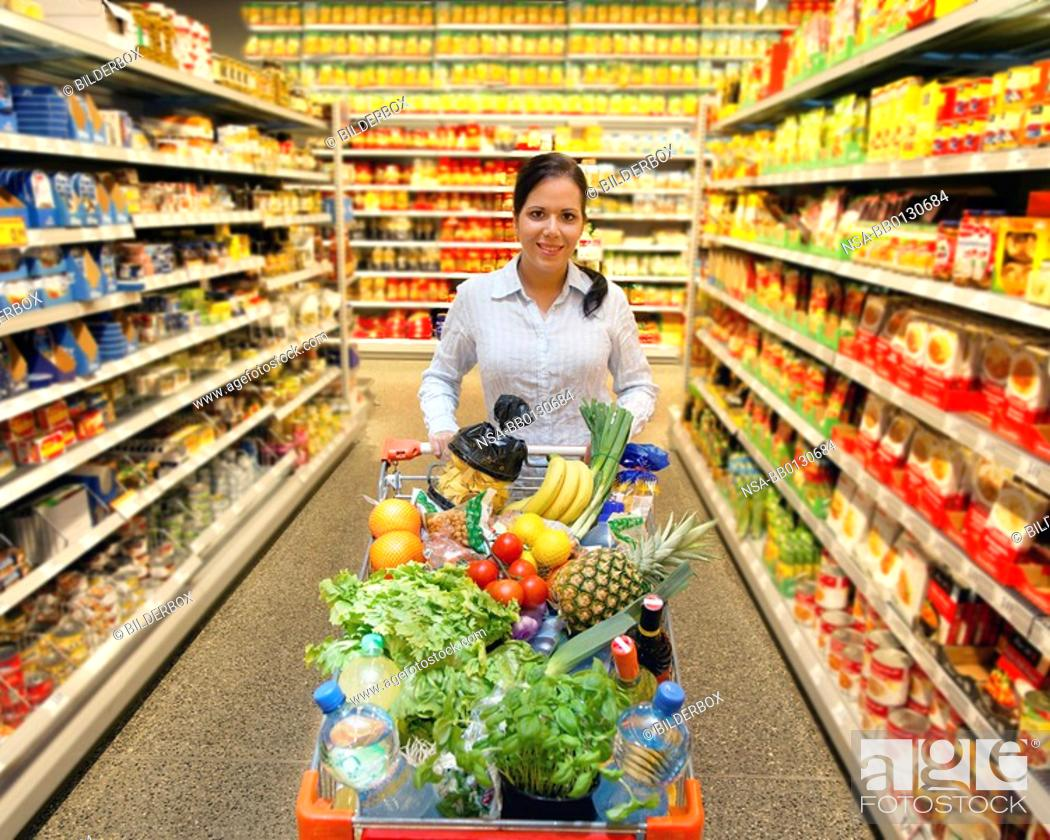Stock Photo: Young woman with shopping cart in the supermarket when shopping.