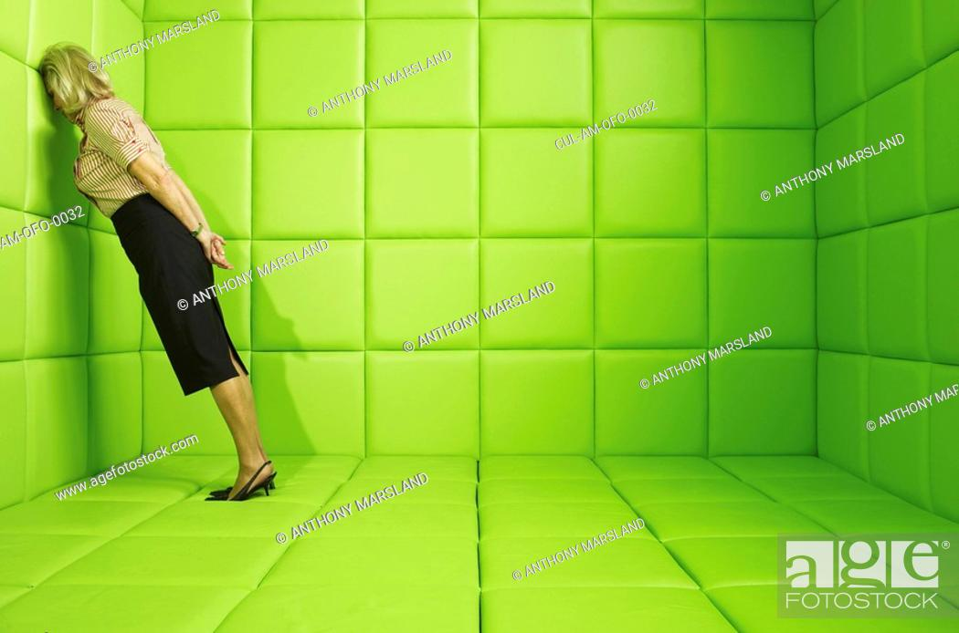 Stock Photo: Woman leaning head against wall in a green padded cell.