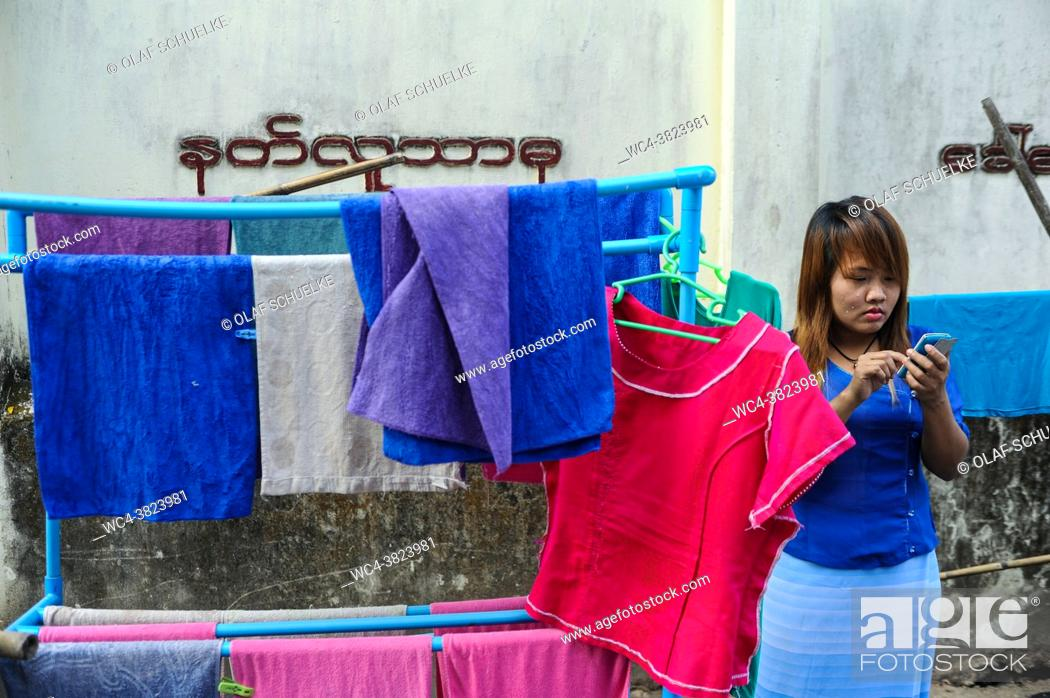 Stock Photo: Yangon, Myanmar, Asia - A young woman stands next to a laundry rack with colourful towels and stares at her smartphone.