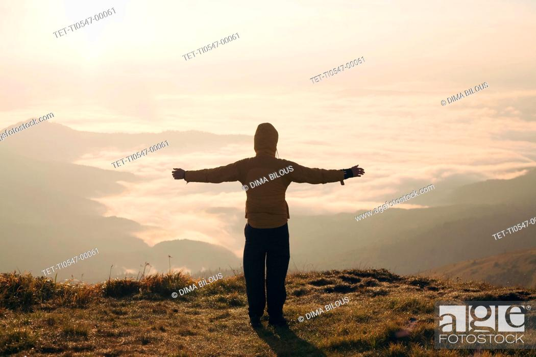 Imagen: Man with arms outstretched in the Carpathian Mountain Range at sunrise.
