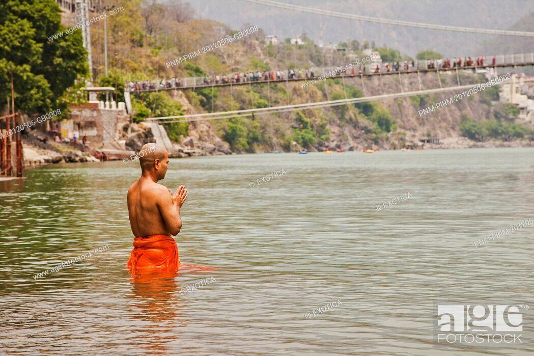 Stock Photo: Hindu monk praying in the sacred waters of holy Ganges River, Ram Jhula, Rishikesh, Uttarakhand, India.