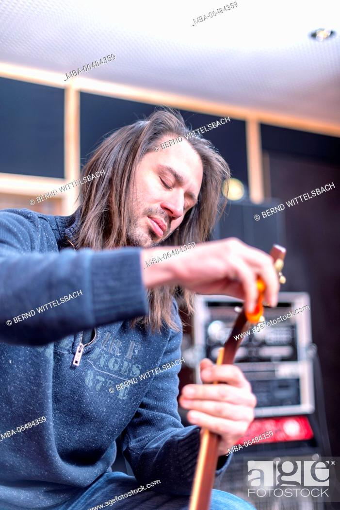Imagen: Musician in the sound studio changing the strings at the guitar,.