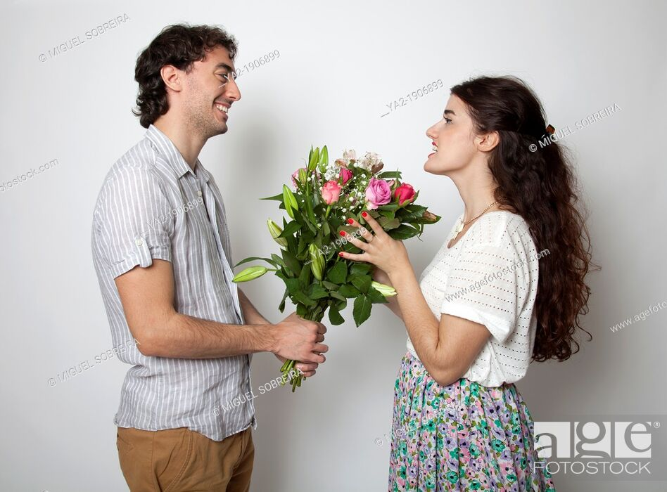 Stock Photo: Man handing bouquet of flowers to woman.