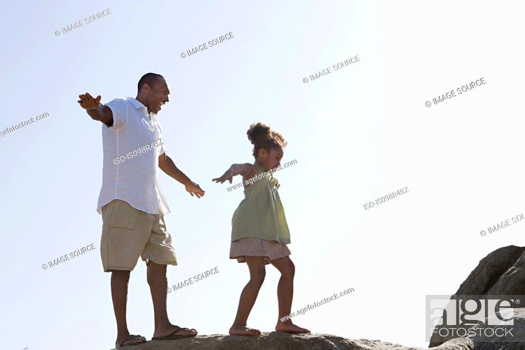 Stock Photo: Father and daughter walking on rocks.