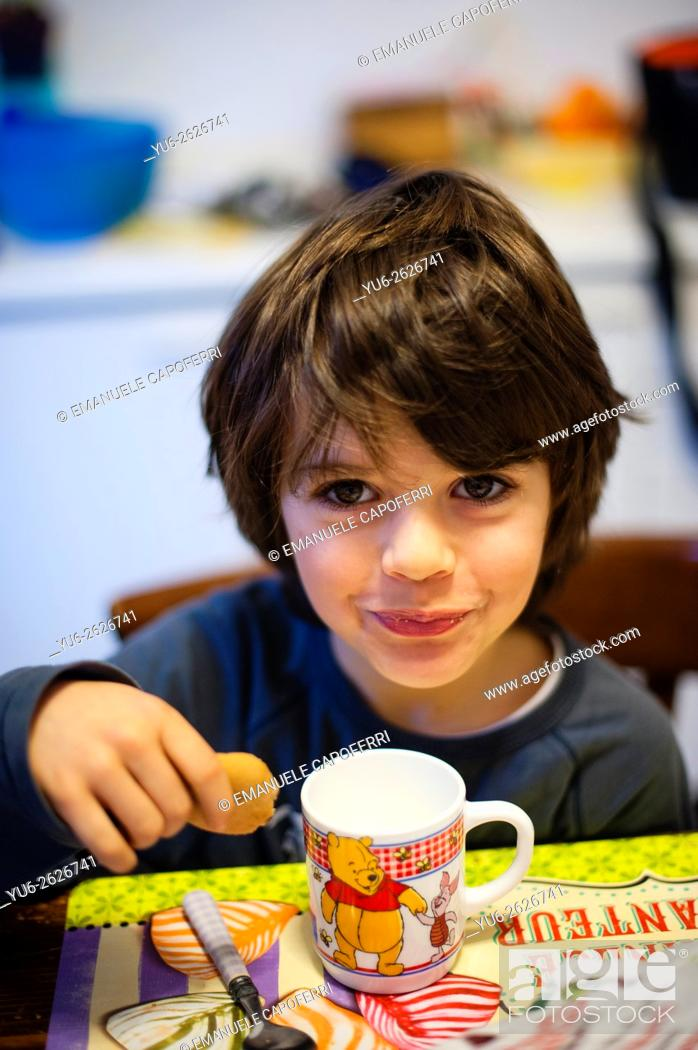 Stock Photo: Child eats milk with breakfast biscuits.