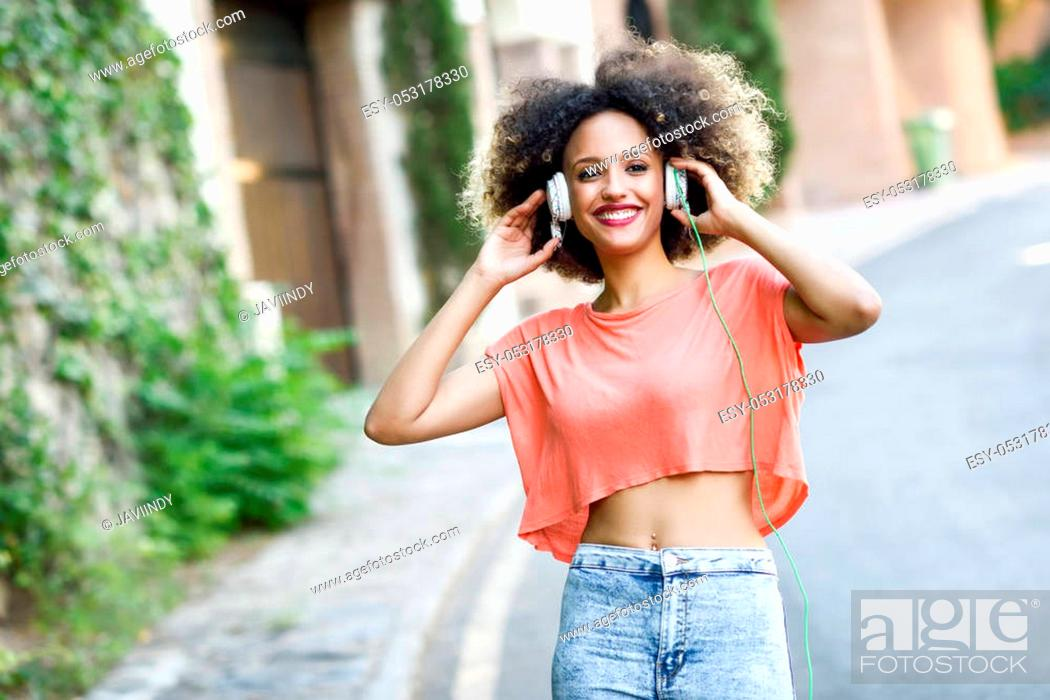 Stock Photo: Portrait of young attractive black girl in urban background listening to the music with headphones. Woman wearing orange t-shirt and blue jeans with afro.