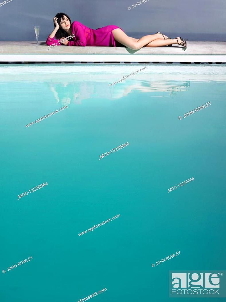 Stock Photo: Woman reclining by pool with champagne glass.