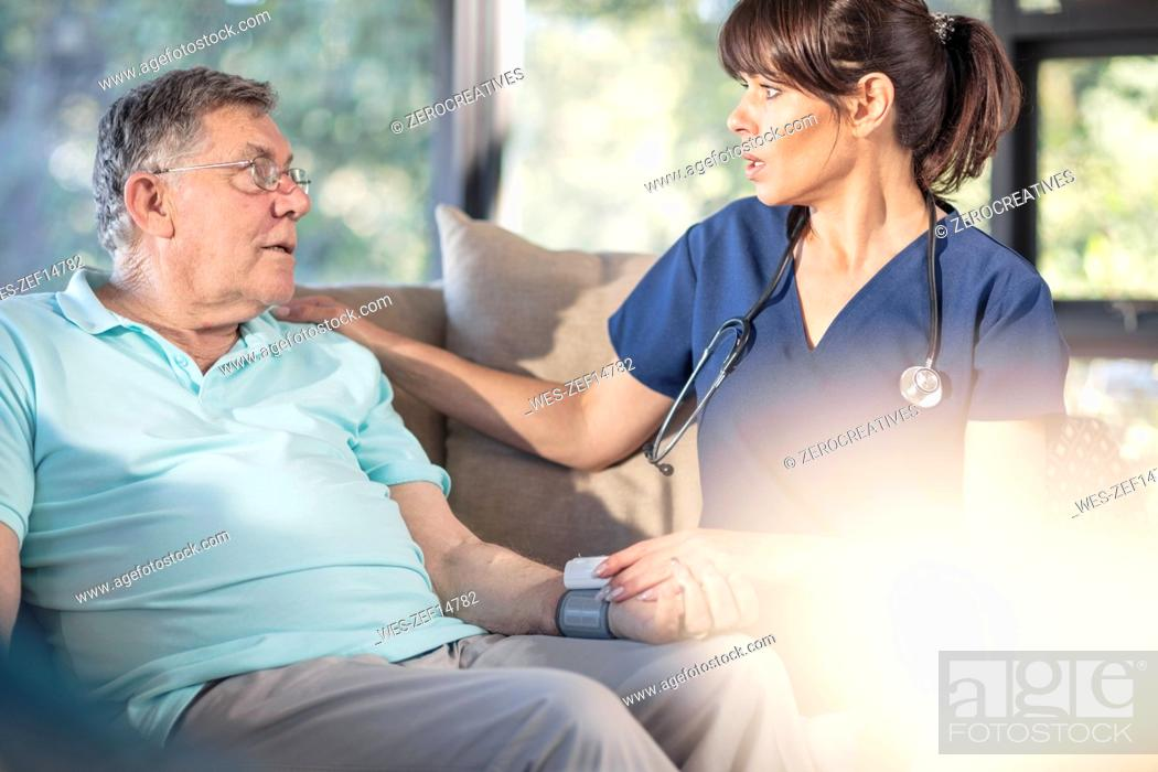 Stock Photo: Nurse caring for of senior patient at home.