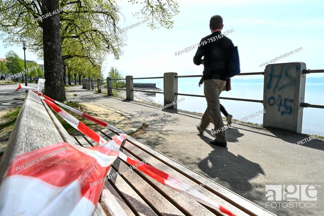 Stock Photo: 13 March 2020, Baden-Wuerttemberg, Friedrichshafen: Passers-by walk along the riverbank promenade, while the bench in the foreground is blocked by fluttering.