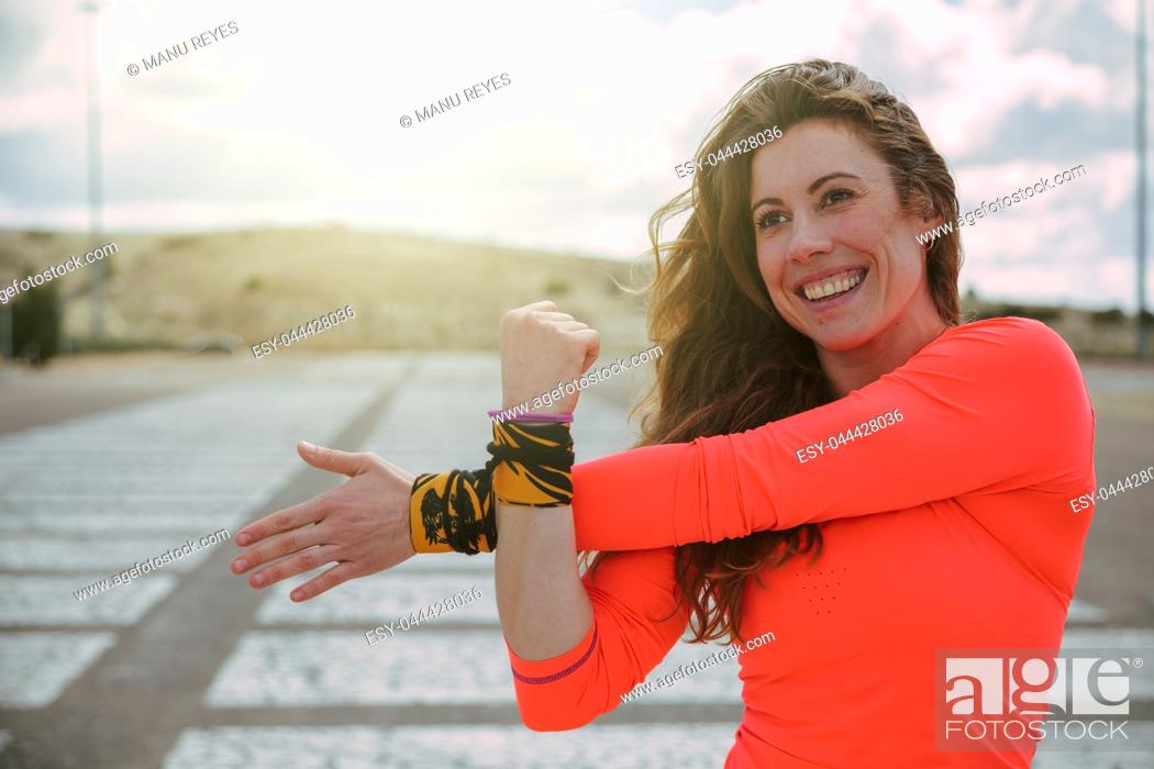 Stock Photo: young woman stretching before running with a orange shirt.
