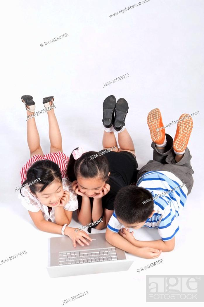 Stock Photo: Child, Children lying on front and using laptop together.