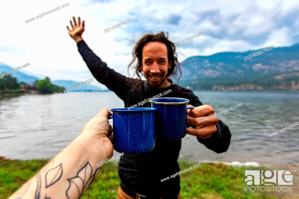Stock Photo: Selective focus of a tattooed person clinching a cup of coffee with a happy young man in front of a beautiful nature scenery outdoors.