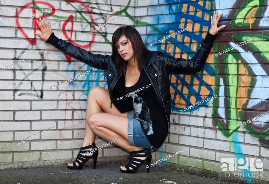 e252cdfcc05 Young woman with dark hair wearing hot pants, a black leather jacket ...