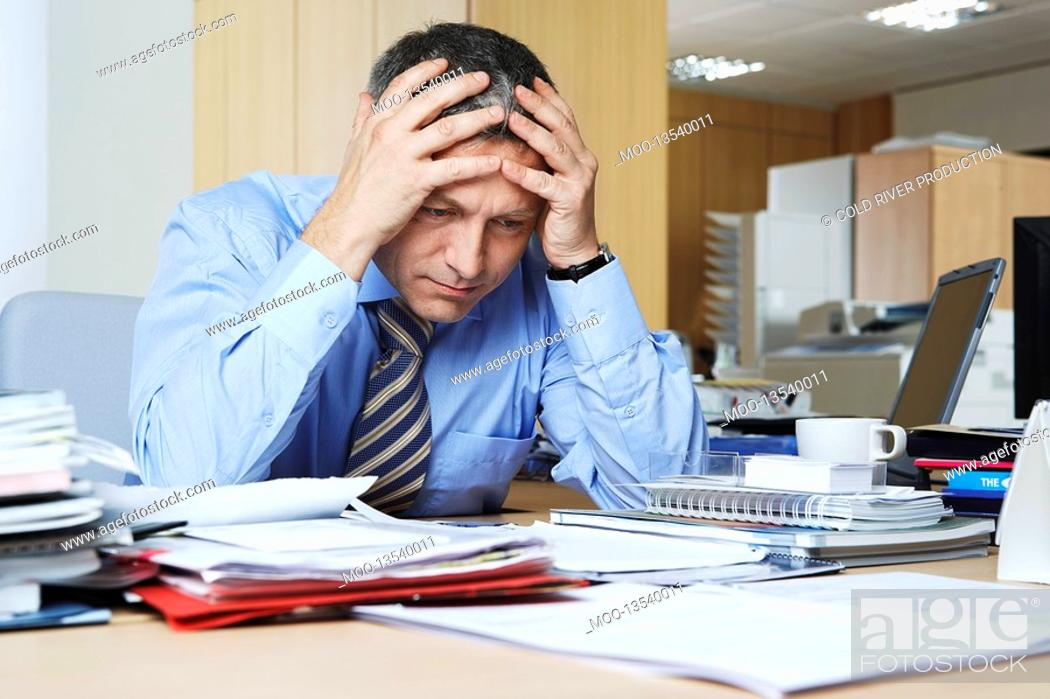 Stock Photo: Businessman sitting at desk with head in hands.