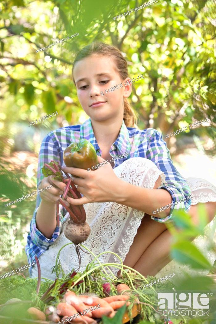 Stock Photo: Girl choosing vegetables from a crate.