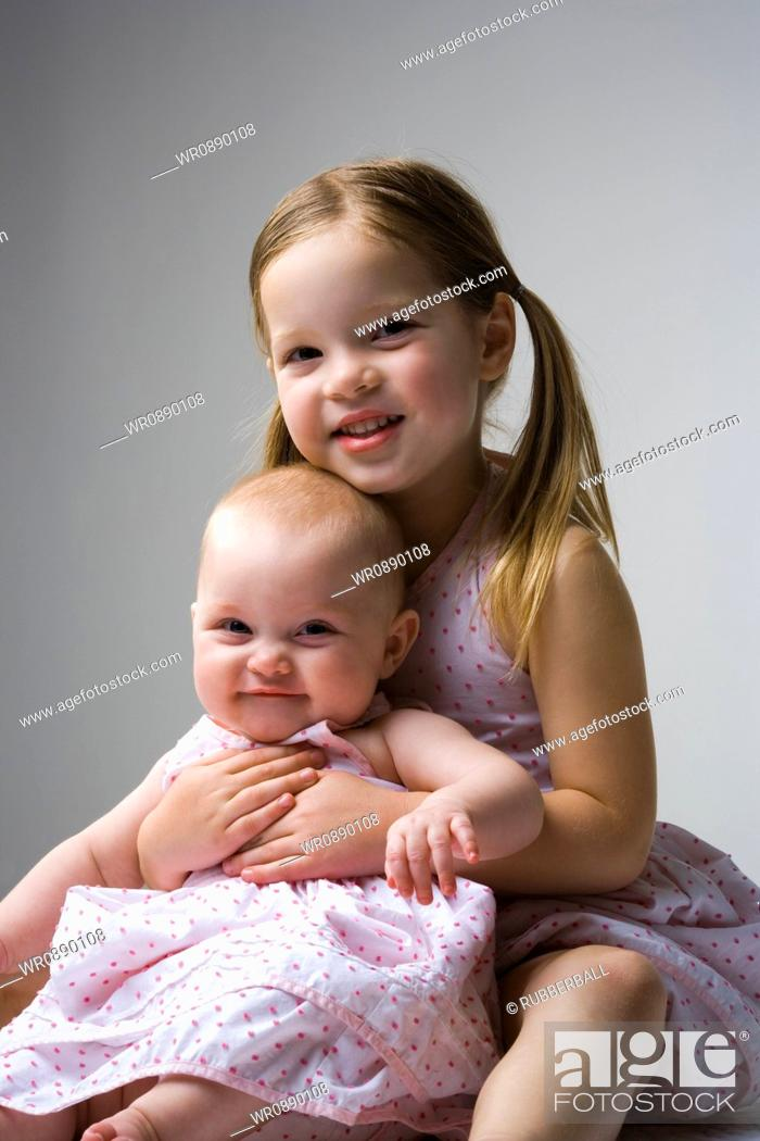 Stock Photo: Portrait of a girl holding a baby girl.