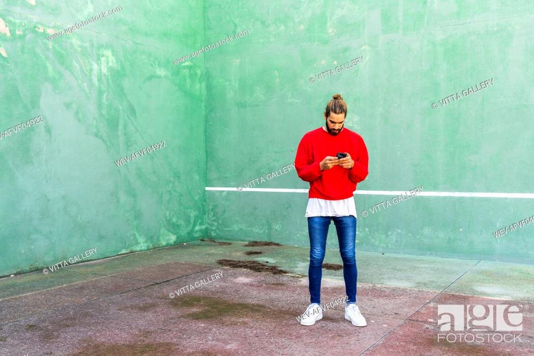 Stock Photo: Young man wearing red sweatshirt raising hands in front of green wall.
